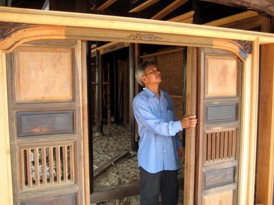 Anh Sáu đang kiểm tra bộ cửa căn nhà lá mái cổ đang được dựng tại phường Quang Trung, TP Quy Nhơn.
